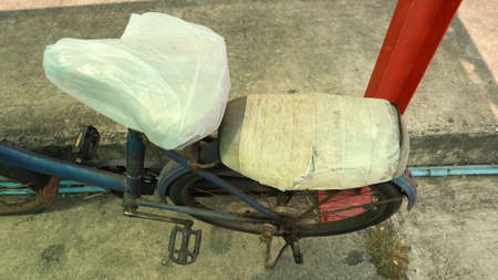 The bicycle seat is damaged, use a plastic bag to cover it.