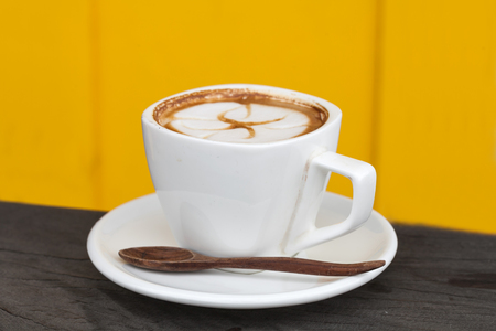 Cup of latte coffee on yellow background photo