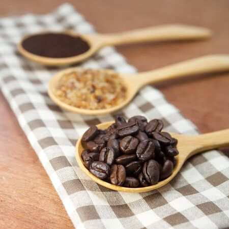 coffee beans and sugar in wooden spoon photo
