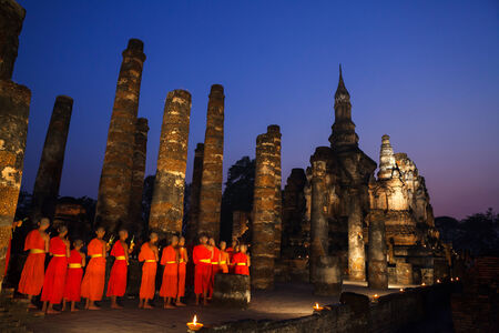 Makha Bucha Day at Sukhothai Historical Park  People walking pass the side of buddha statue in wian tian ceremony photo