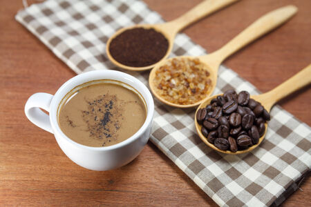 coffee beans and sugar in wooden spoon with cup of coffee photo