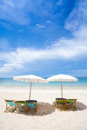Liegestühle auf dem weißen Sandstrand mit bewölkten blauen Himmel