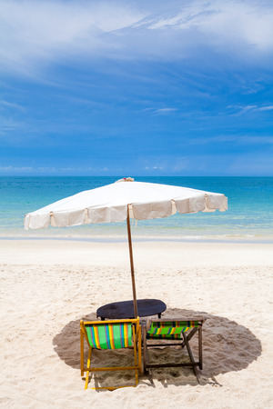 Beach chairs on the white sand beach with cloudy blue sky  photo