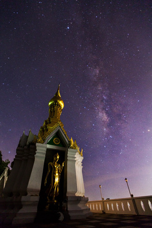 vulpecula: Milky Way at Standing gold Buddha image name is Wat Sra Song Pee Nong in Phitsanulok, Thailand   Stock Photo
