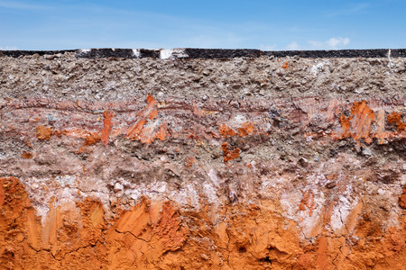 Layer of soil beneath the asphalt road with blue sky photo