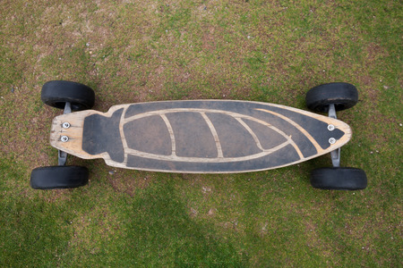 Old wooden skateboard on grass photo