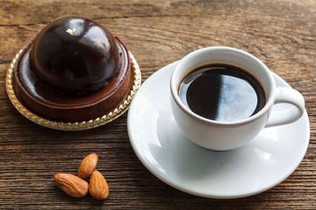 invigorate: Coffee with chocolate cake and almonds on wood background