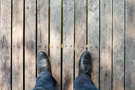 moccasins: two legs wearing moccasins  and denim jeans on wooden background