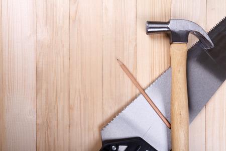 serrucho: serrucho, martillo de orejas y l�piz sobre fondo de madera escritorio