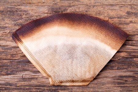 coffee filter: Coffee filter with brewed coffee on wood background