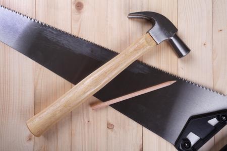 serrucho: serrucho, martillo de orejas y lápiz sobre fondo de madera escritorio