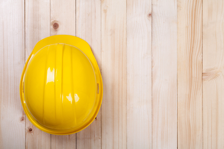 architect: yellow hardhat architect on brown wood background