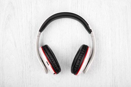audifonos: Auriculares Bluetooth en el fondo de madera blanca Foto de archivo
