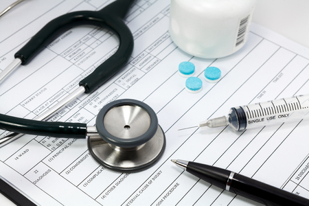 high cost of healthcare: stethoscope syringe and pills on blank Patient information