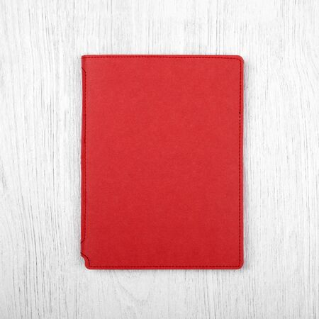 spread sheet: red notebook on white wooden table, top view