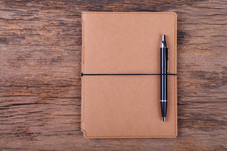 Blank note pad with pen on wood background