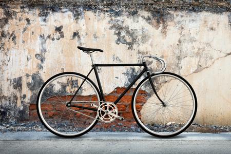 clavados: bicicleta fija del engranaje de la ciudad y quebró el fondo de muro de hormigón de edad Foto de archivo