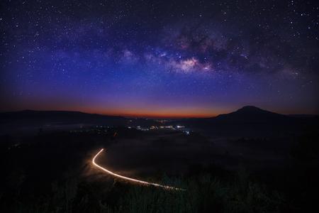 Milky way galaxy with lighting on the road at Khao Takhian Ngo View Point at Khao-kho Phetchabun,Thailand, Long exposure photograph Stock Photo