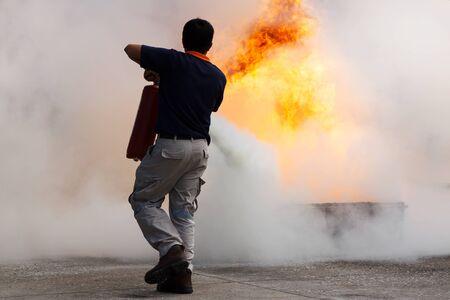 extinguishing: firefighter extinguishing a fire Stock Photo