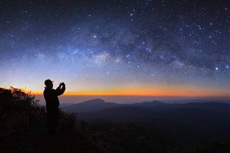 A man take photo milky way galaxy at Doi inthanon Chiang mai, Thailand. Long exposure photograph. With grain