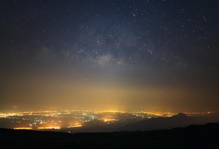 Milky way galaxy and city light at Phutabberk Phetchabun in Thailand.Long exposure photograph.With grain