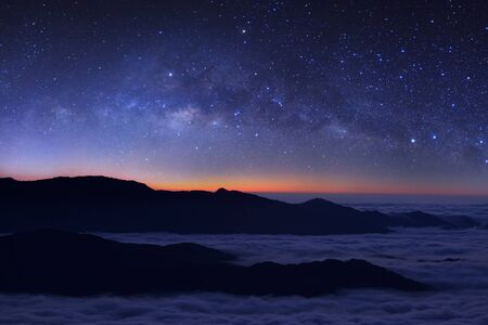Milky way galaxy over foggy mountains in Thailand. Long exposure photograph.with grain Stock Photo