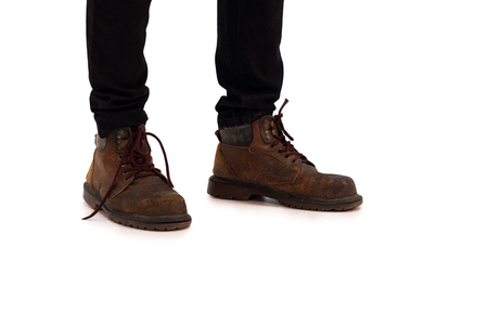 Young fashion mans legs in black jeans and brown boots