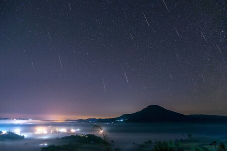 Geminid Meteor in the night sky with moon and fog at Khao Takhian Ngo View Point at Khao-kho Phetchabun,Thailand 스톡 콘텐츠