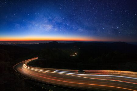 Milky way galaxy with stars and space dust in the universe and lighting on the road before morning at Doi inthanon Chiang mai, Thailand