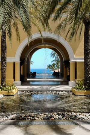 cabo: View of ocean therough archway, courtyard and fountain in Cabo San Lucas, Mexico