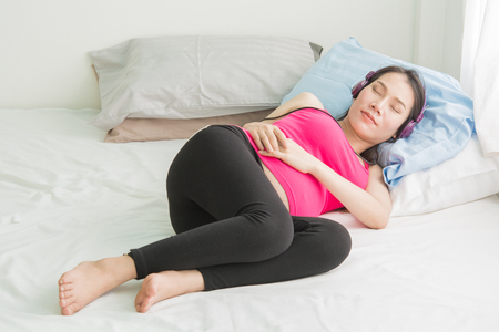 Pregnant women listen to music on the phone.on bed at a room