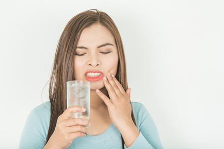 Sensitive teeth in woman And a glass of cold water