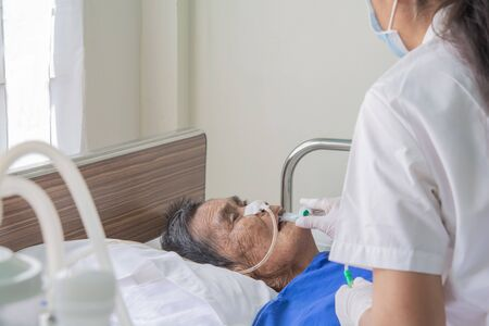 Patients in bed and nurses are preparing to suck up the airways and lungs in the old aged patients.