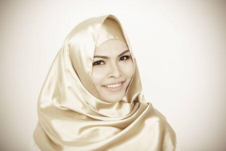 Fille souriante en hijab couvrant belle avec bonheur et mur de couleur