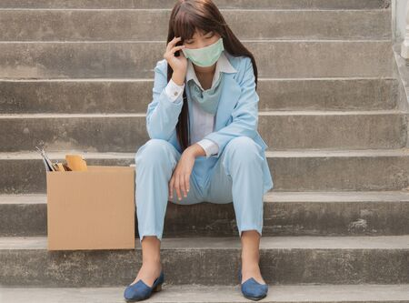 The girl sits sadly on the cement stairs and who are unemployed in economic conditions have problems and epidemics. Stock Photo