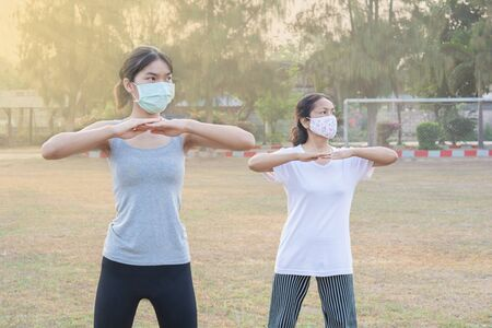 Two women wearing masks exercising in the morning In the park and solar nature. And good health for new Normal and lifestyle