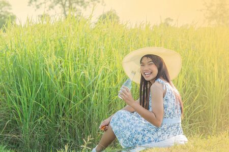 The girl is wearing a white dress in native thai style pattern painting pants  and a hat to drink in the green rice fields and the soft sunlight.