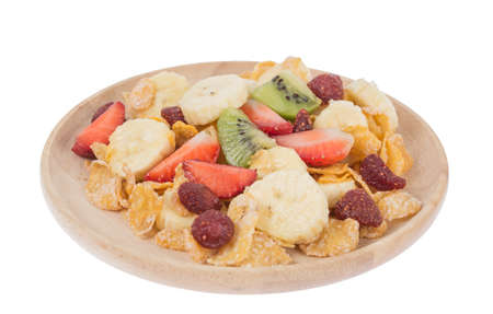 Cereal and fruit and milk on a wooden plate