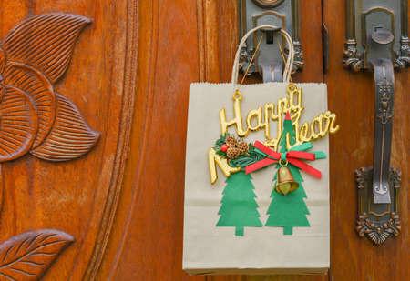 Gift in a Christmas paper bag hanging on the door. Standard-Bild