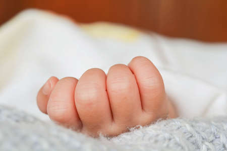Baby hand on bed