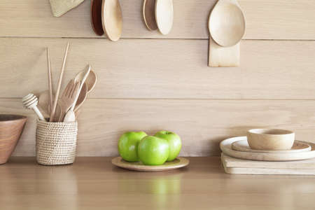 Green Apple in plate on wood table in the kitchen. Banco de Imagens