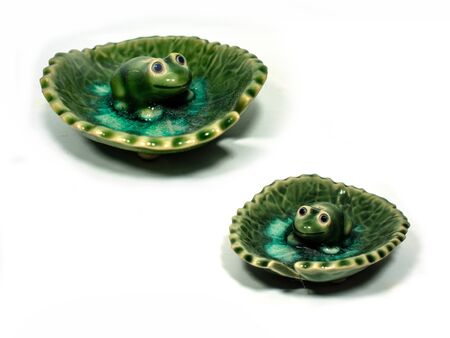 potent: Incense made of ceramic green frog sitting on a lotus leaf .