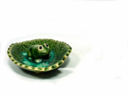 odour: Incense made of ceramic green frog sitting on a lotus leaf .