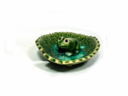stench: Incense made of ceramic green frog sitting on a lotus leaf .