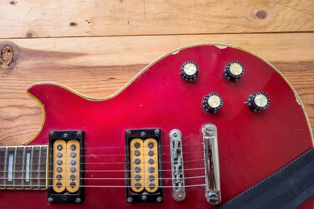 humbucker: Vintage red guitar on old wood surface.