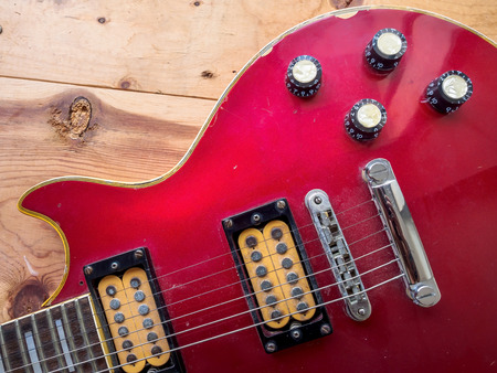 riff: Vintage red guitar on old wood surface.