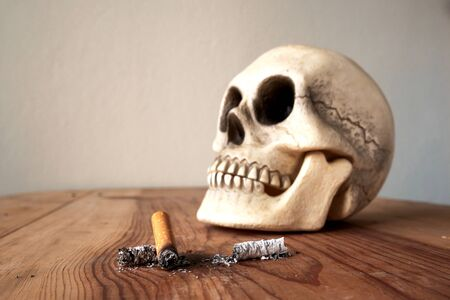 stub: Close up of cigarette stub and blured  human skull Stock Photo