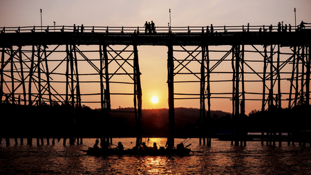 Silhouetted bridge at sunset in Sangkla,Thailand Stock Photo
