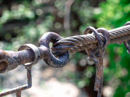 Rusty sling hook  and knots close, bolts used to mount the bridge rail.