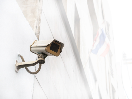 Old and dirty cctv camera installed outside the building Stock Photo